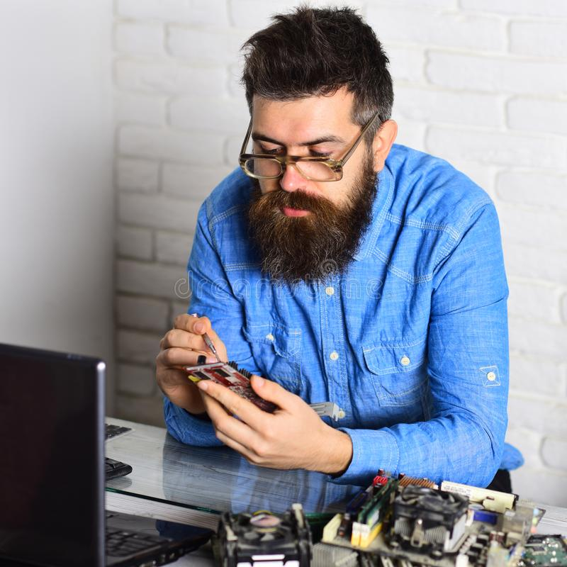 Master of computers. Bearded hipster works on fixing digital hardware. Assemblying of electronic devices. Bearded man. Repair circuit board. Engineer or royalty free stock photo