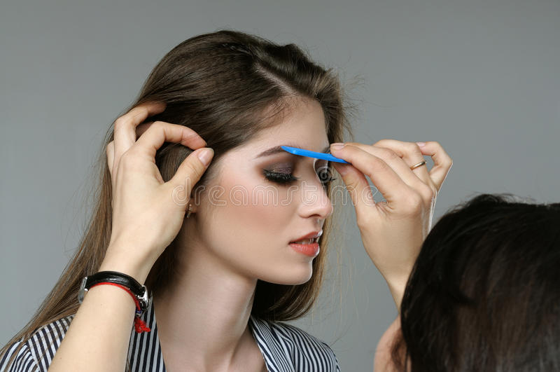 Master corrects the eyebrows of the model before shooting. stock image