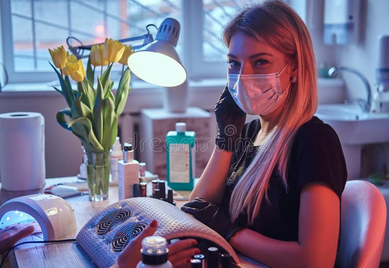 Master cosmetologist in mask and gloves sits at the manicure table and looks at the camera. royalty free stock images