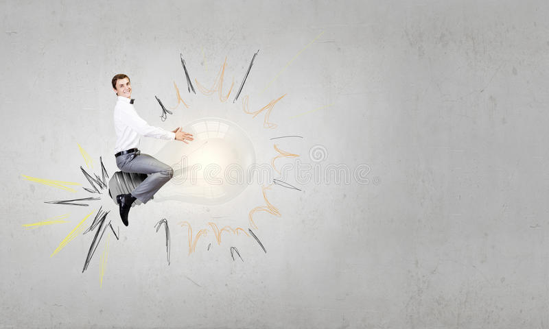 Master of creative ideas. Conceptual image of young businessman riding light bulb royalty free stock image