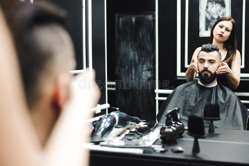 Master cuts hair and beard of men in the barbershop, hairdresser makes hairstyle for a young man. Master cuts hair and beard of men in the barbershop stock photography