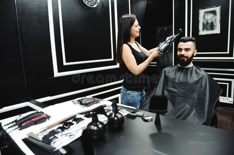 Master cuts hair and beard of men in the barbershop, hairdresser makes hairstyle for a young man. Master cuts hair and beard of men in the barbershop stock photo