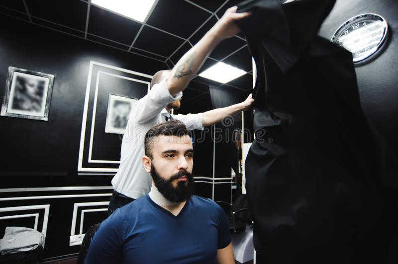 Master cuts hair and beard of men in the barbershop, hairdresser makes hairstyle for a young man. Master cuts hair and beard of men in the barbershop royalty free stock photos