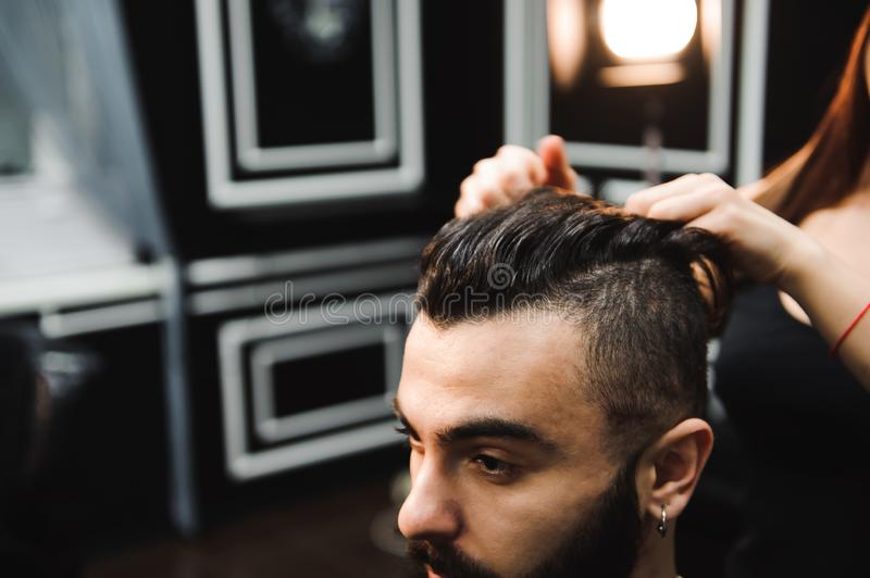 Master cuts hair and beard of men in the barbershop, hairdresser makes hairstyle for a young man. Master cuts hair and beard of men in the barbershop royalty free stock image