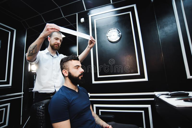 Master cuts hair and beard of men in the barbershop, hairdresser makes hairstyle for a young man. Master cuts hair and beard of men in the barbershop stock photos