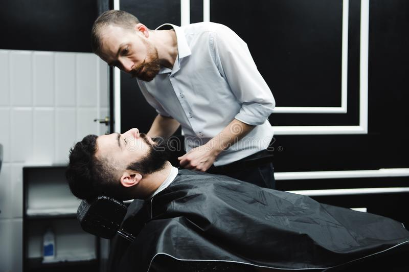 Master cuts hair and beard of men in the barbershop, hairdresser makes hairstyle for a young man. Master cuts hair and beard of men in the barbershop royalty free stock photography