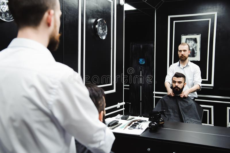 Master cuts hair and beard of men in the barbershop, hairdresser makes hairstyle for a young man. Master cuts hair and beard of men in the barbershop royalty free stock photo