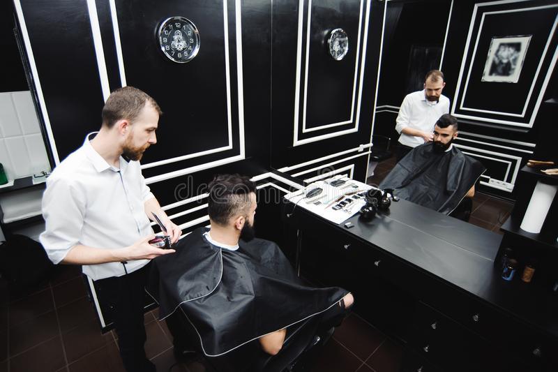 Master cuts hair and beard of men in the barbershop, hairdresser makes hairstyle for a young man. stock photos