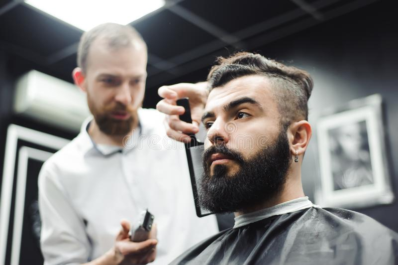 Master cuts hair and beard of men in the barbershop, hairdresser makes hairstyle for a young man. stock image