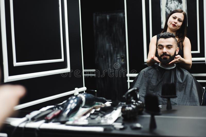 Master cuts hair and beard of men in the barbershop, hairdresser makes hairstyle for a young man. Master cuts hair and beard of men in the barbershop stock images