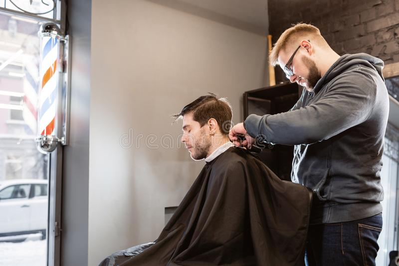 Master cuts hair and beard of men in the barbershop, hairdresser makes hairstyle for a young man. Barber work with stock images