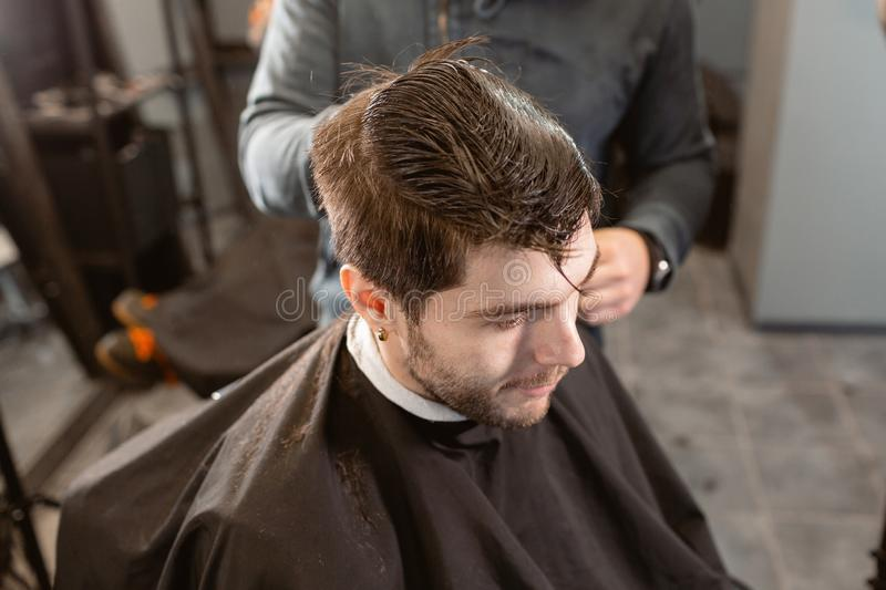 Master cuts hair and beard of men in the barbershop, hairdresser makes hairstyle for a young man. Barber work with. Hair cutting with metal scissors. Master cuts stock photography