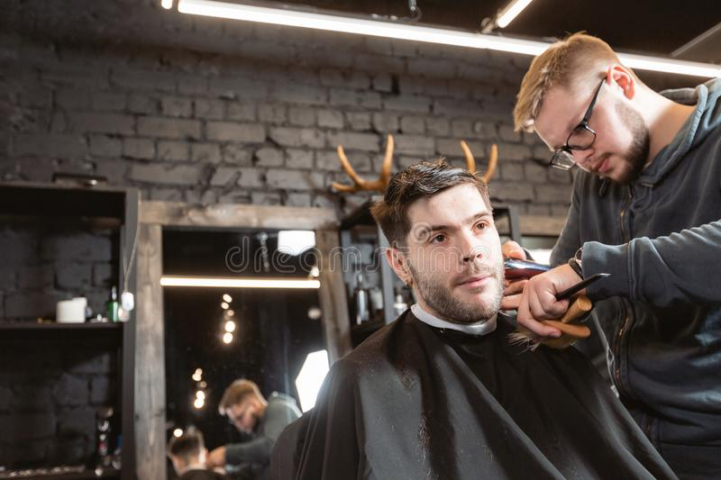 Master cuts hair and beard of men in the barbershop, hairdresser makes hairstyle for a young man. Barber work with. Hair cutting with metal scissors. Master cuts royalty free stock photos