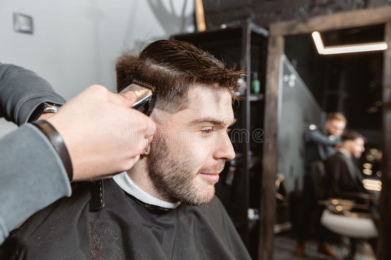 Master cuts hair and beard of men in the barbershop, hairdresser makes hairstyle for a young man. Barber work with. Hair cutting with metal scissors. Master cuts stock image