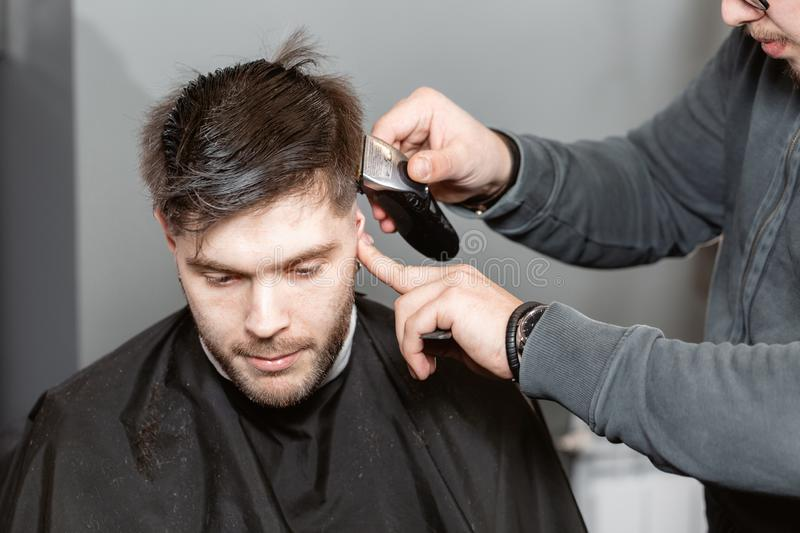 Master cuts hair and beard of men in the barbershop, hairdresser makes hairstyle for a young man. Barber work with. Hair cutting with metal scissors. Master cuts royalty free stock photography