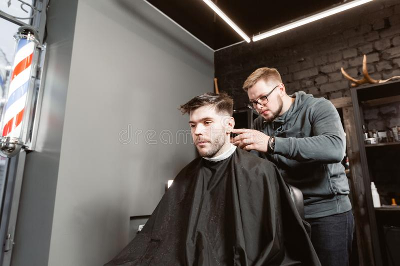 Master cuts hair and beard of men in the barbershop, hairdresser makes hairstyle for a young man. Barber work with. Hair cutting with metal scissors. Master cuts stock photos