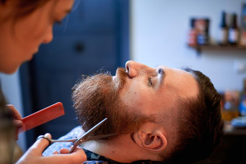 Master cuts hair and beard of men in the barbershop royalty free stock image