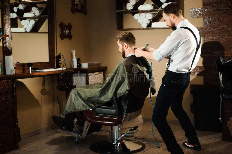 Master cuts hair and beard of men in the barbershop stock image