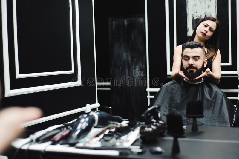 Master cuts hair and beard of men in the barbershop, hairdresser makes hairstyle for a young man. Master cuts hair and beard of men in the barbershop royalty free stock images