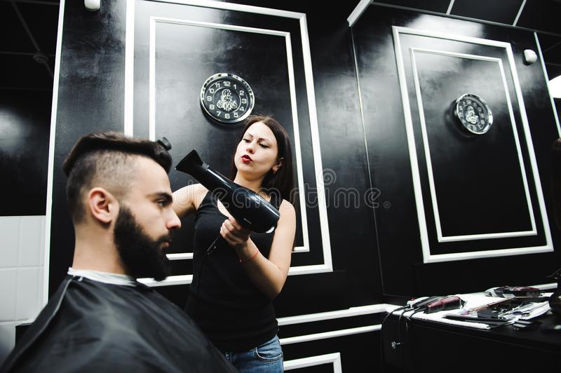 Master cuts hair and beard of men in the barbershop, hairdresser makes hairstyle for a young man. Master cuts hair and beard of men in the barbershop stock image