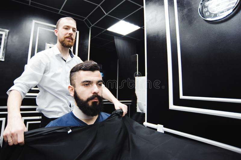 Master cuts hair and beard of men in the barbershop, hairdresser royalty free stock images