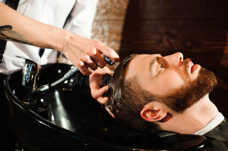 Master cuts hair and beard of men in the barbershop royalty free stock photography