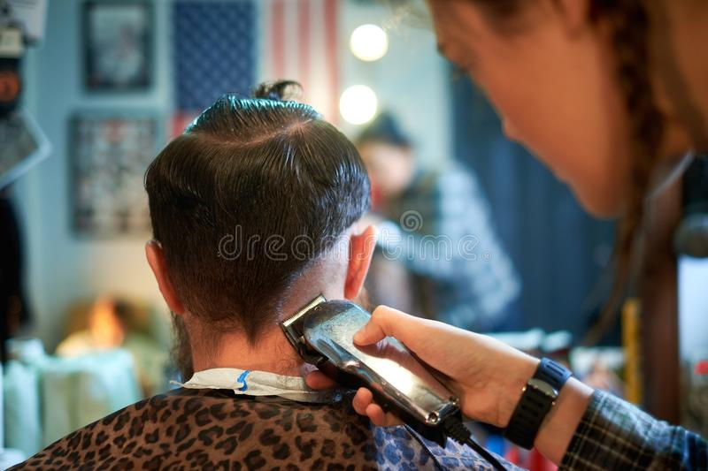 Master cuts hair and beard of men in the barbershop royalty free stock photo