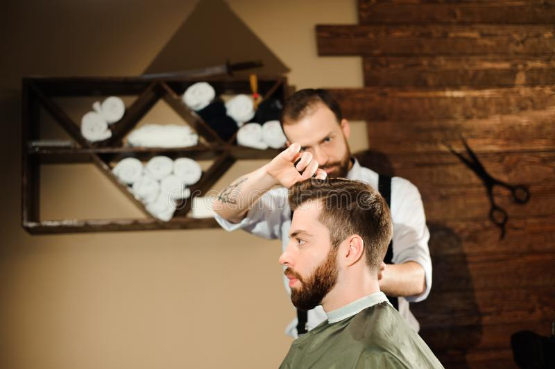 Master cuts hair and beard of men in the barbershop stock photo