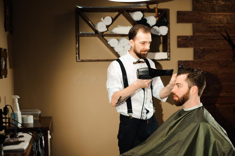 Master cuts hair and beard of men in the barbershop stock photography