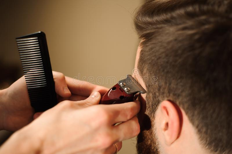 Master cuts hair and beard of men in the barbershop stock images