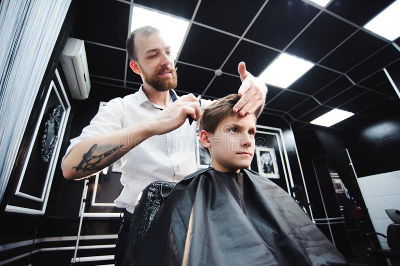 Master cuts hair of a boy in the barbershop, hairdresser makes hairstyle for a boy stock image