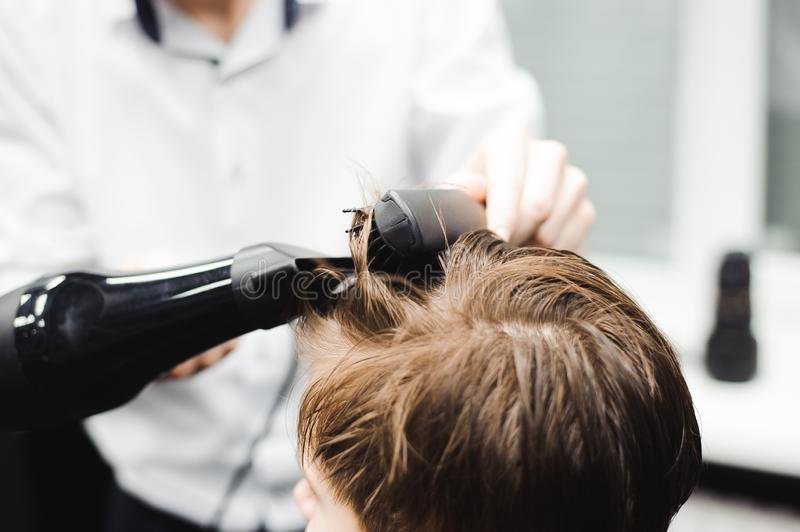Master cuts hair of a boy in the barbershop, hairdresser makes hairstyle for a boy.  royalty free stock photography