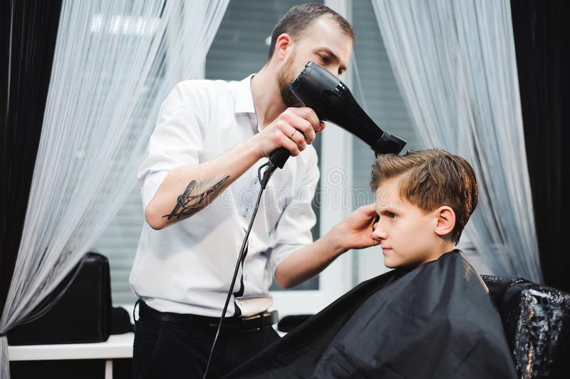 Master cuts hair of a boy in the barbershop, hairdresser makes hairstyle for a boy. Master cuts hair of a boy in the barbershop, hairdresser makes hairstyle for stock photo