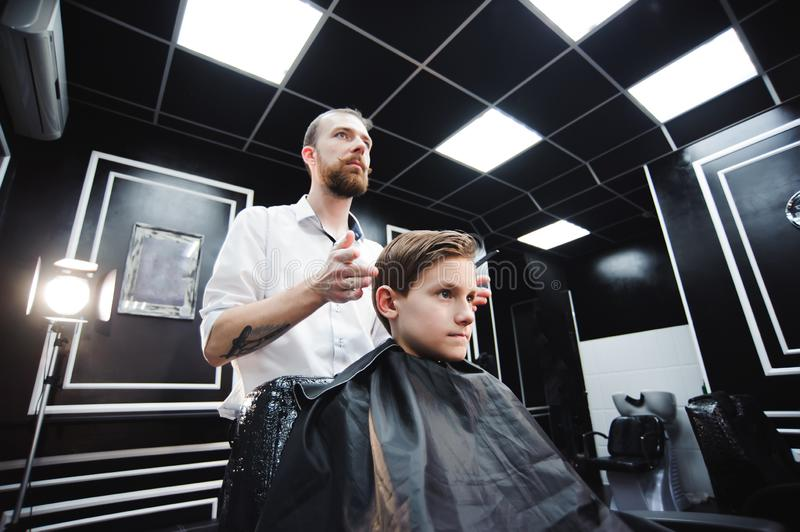 Master cuts hair of a boy in the barbershop, hairdresser makes hairstyle for a boy. Master cuts hair of a boy in the barbershop, hairdresser makes hairstyle for royalty free stock photo