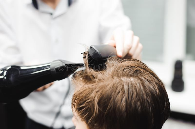 Master cuts hair of a boy in the barbershop, hairdresser makes hairstyle for a boy. Master cuts hair of a boy in the barbershop, hairdresser makes hairstyle for stock images
