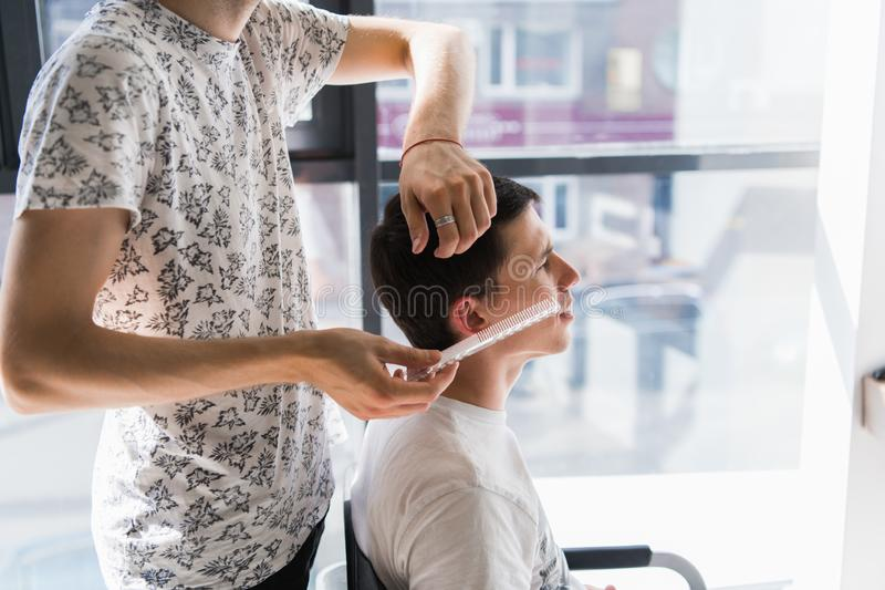 Master cuts hair of man in the barbershop, hairdresser makes hairstyle for a young man stock images