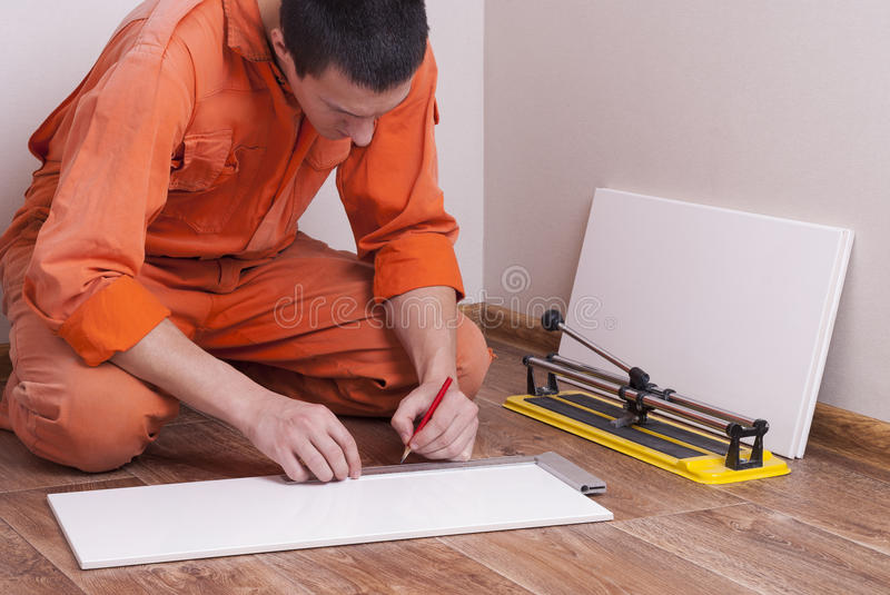Master cuts the tile. With a tile cutter royalty free stock photography