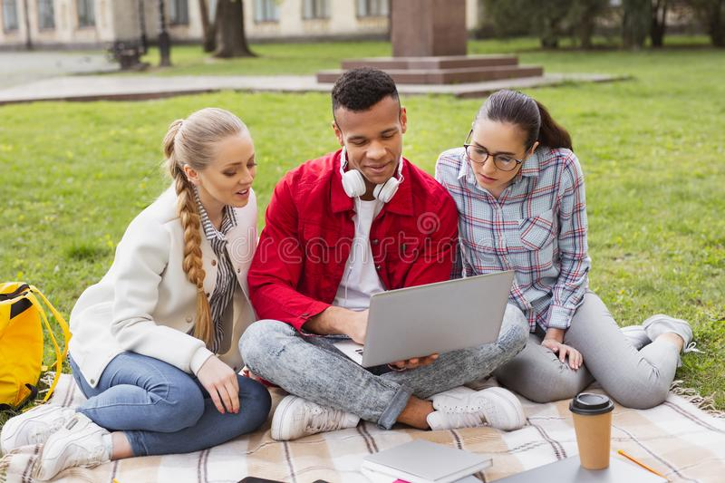 Master degree students watching memorable photos on laptop royalty free stock photos
