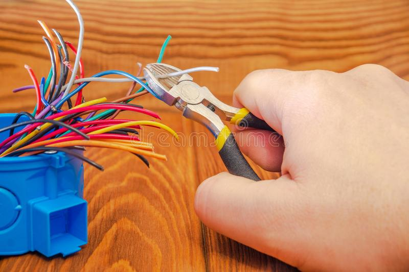 Master electrician cuts a wire in junction box royalty free stock photography
