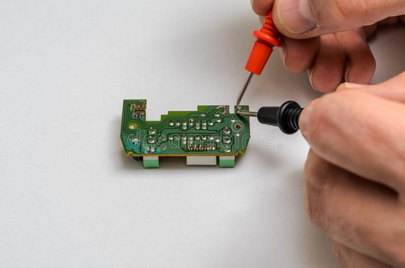 Master engineer tests and repairs microchip with multimeter stock images
