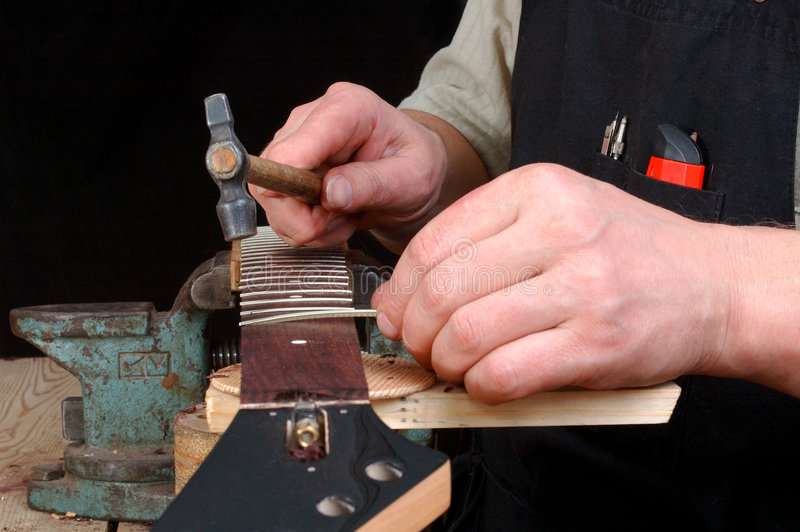 luthier establish frets in the neck of the guitar stock image