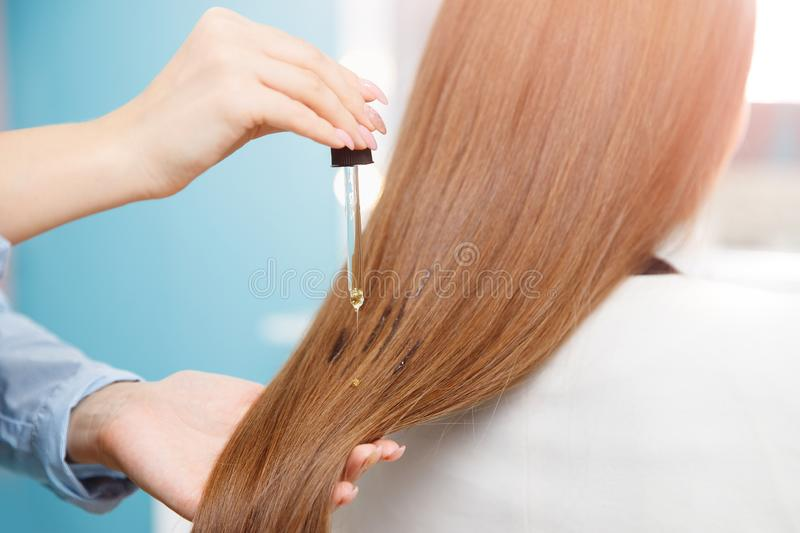 Master hairdresser applies oil to hair care for and restore growth of cuticles woman. royalty free stock photo