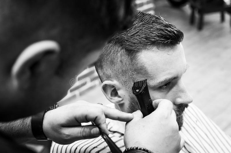 Master hairdresser cuts a man in the salon stock images