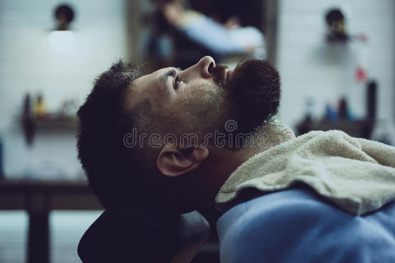 Master hairdresser does hairstyle and style with scissors and comb. Barber making haircut of attractive bearded man in stock photography
