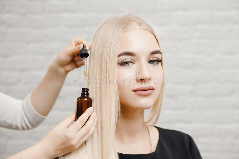 Master hairdresser procedure oil hair treatment for woman. Concept spa salon. Master hairdresser procedure oil hair treatment for woman. Concept spa salon royalty free stock images