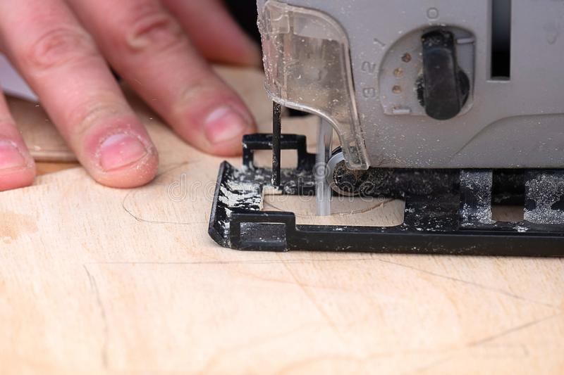 The master holds an electric jigsaw with the other hand supports the workpiece royalty free stock photo