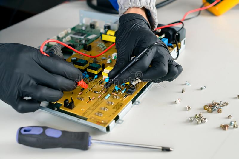 Master is looking for damage, repair office equipment using multimeter. stock image