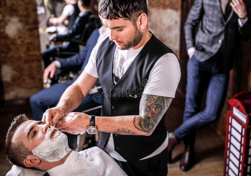 Master makes beards correction in barbershop salon. Close up photo. royalty free stock photo