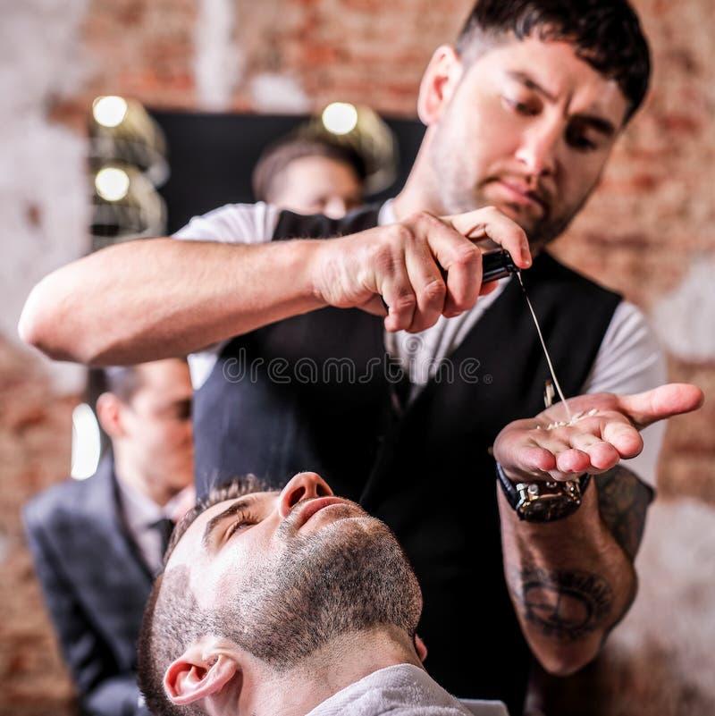 Master makes beards correction in barbershop salon. Close up photo. royalty free stock photography