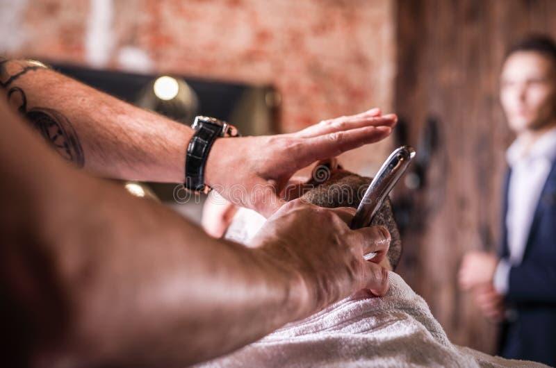 Master makes beards correction in barbershop salon. Close up photo. stock photography